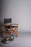 Der Stuhl des Filmregisseurs mit Filmspule Stockfotografie