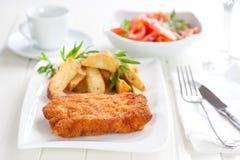 Schnitzel com cunhas e salada do tomate Imagens de Stock Royalty Free