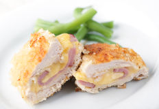 Schnitzel Cordon bleu. Chicken schnitzel Cordon blue with green beans on white plate closeup Royalty Free Stock Images