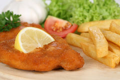 Schnitzel cutlet meal with french fries, lemon and lettuce Royalty Free Stock Image