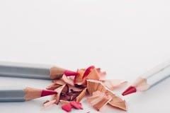 Schnitzel des kosmetischen rosa Bleistifts und der farbigen Bleistifte auf weißem Hintergrund Stockfotos