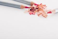 Schnitzel des kosmetischen rosa Bleistifts und der farbigen Bleistifte auf weißem Hintergrund Lizenzfreie Stockfotografie