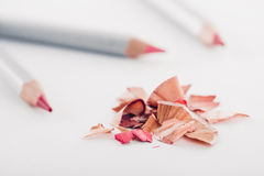 Schnitzel des kosmetischen rosa Bleistifts und der farbigen Bleistifte auf weißem Hintergrund Lizenzfreie Stockbilder