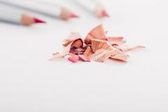 Schnitzel des kosmetischen rosa Bleistifts und der farbigen Bleistifte auf weißem Hintergrund Stockbilder