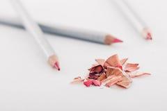 Schnitzel des kosmetischen rosa Bleistifts und der farbigen Bleistifte auf weißem Hintergrund Stockbild