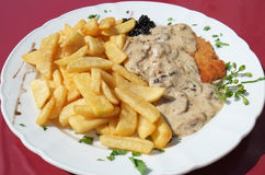 Schnitzel dinner. A schnitzel with a mushroom cream sauce, served with fries Stock Image
