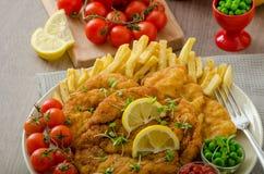 Schnitzel, fransmansmåfiskar och microgreenssallad Royaltyfri Foto