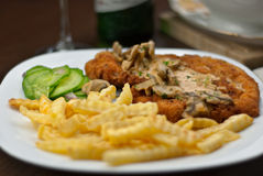 Schnitzel, french fries and cuccumber salat with jaeger sauce stock photo
