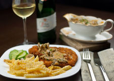 Schnitzel, french fries, cucumber salat and white wine with jaeger sauce stock photo