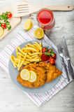 Schnitzel with french fries and a spicy dip Royalty Free Stock Photos