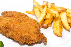 Schnitzel with fries. Schnitzel with french fries on a white plate in a restaurant royalty free stock image