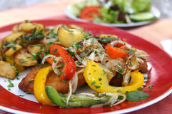 Schnitzel. (German escalope) with fried peppers, onions and potatoes Stock Image