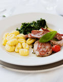 Schnitzel with gnocchi and spinach. Shot inside stock photos