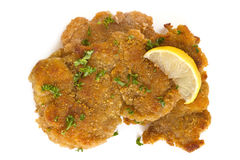 Schnitzel with Lemon. Schnitzel, garnished with lemon and parsley, isolated on white Stock Photos