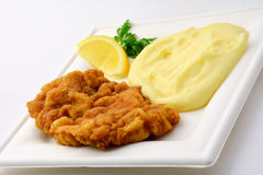 Schnitzel with mashed potato on white square plate, isolated Stock Image