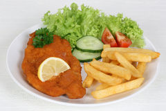 Schnitzel meal with french fries, salad and lemon Stock Photo