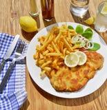 Schnitzel med franska småfiskar arkivfoton