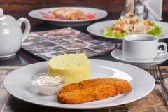 Schnitzel met fijngestampte aardappels en witte saus stock fotografie