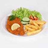 Schnitzel met frieten en salade op plaat Royalty-vrije Stock Afbeeldingen