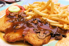 Schnitzel with muchroom sauce. Plate of traditional schnitzel with mushroom sauce and potato fries Stock Photography
