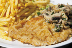 Schnitzel with mushrooms and chips, close up royalty free stock photos