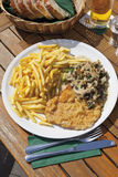 Schnitzel with mushrooms and chips in plate Stock Photo