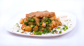 Schnitzel with potatoes on a plate. Schnitzel with potatoes and greens on a plate Royalty Free Stock Images