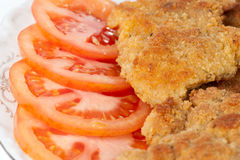 Schnitzels and sliced tomato, close-up Stock Photo