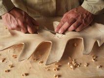 Schnitzen eines Blattes im Holz stockbild