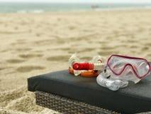 Schnorchel und Tauchmaske auf einem deckchair auf einem weißen Sand setzen auf den Strand Stockfotografie