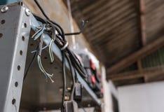 Schnur der elektrischen Leistung, einige mit BRITISCHE Stecker gesehenem hängendem Metallfach in einer Werkstatt stockfoto