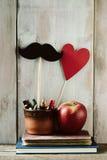 Schnurrbart, Herz, Bleistifte, Apfel und Bücher Stockbild