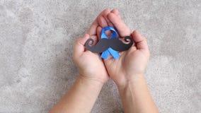 Schnurrbartmuster mit Symbol des blauen Bandes in Kind-` s Händen movember Konzept Prostatakrebs und -männer ` s Gesundheitsbewus