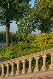 Schodki z poręczami w antyka stylu w parku na tle bogactwo zieleni dąb opuszczają Obrazy Royalty Free