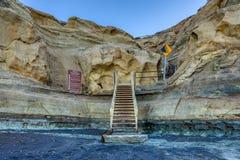 Schodki zapewniają ścieżkę dla wycieczkowiczy unosić się od plaży w górę brąz falez obraz stock
