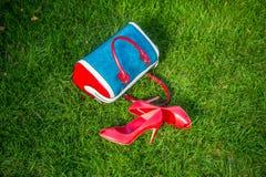 Schoenen en van vrouwen de handtas legt op het gras, de schoenen van vrouwen royalty-vrije stock foto's