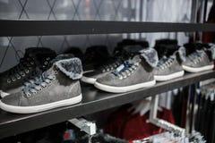 Schoenen - grijze tennisschoenen op de plank in de opslag Stock Foto's