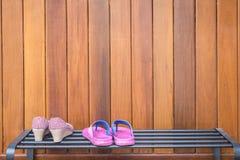 Schoenen op de zwarte plank van metaalschoenen op houten achtergrond Royalty-vrije Stock Foto's