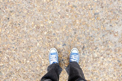 Schoenen op rotsachtige grond en zwarte Jeans Stock Foto