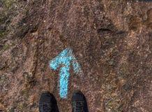 Schoenen van een menselijke status bij een blauwe geschilderde richtingspijl ter plaatse royalty-vrije stock fotografie