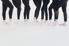Schoenen van het balletdanser de bindende ballet Sluit balletmeisje omhoog het zetten op haar pointeschoenen zittend op de vage v stock afbeelding