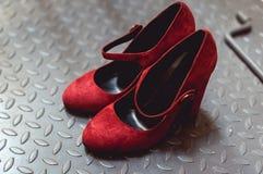 Schoenen van het leerpompen van dames omhoog sluiten de rode gemzen op een metaalachtergrond, Stock Foto's