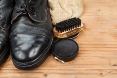 Schoenpoetsmiddel met borstel, doek en versleten laarzen op houten platform Stock Foto