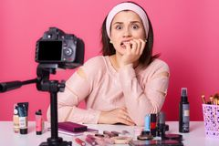 Schoked a effrayé la femelle d'une chevelure noire posant dans le studio autour des cosmétiques, vidéo de enregistrement, se sent photo stock