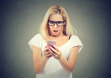 Schokierende Meldung Überraschte Frau des blonden Haares, die Handy hält und entlang er anstarrt stockbild