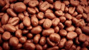 Schokoladeüberzogene Erdnüsse gossen in Stapel stock footage