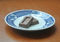 Schokolade auf Platte auf Holztisch lizenzfreie stockbilder