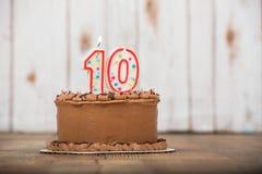 Schokolade bereifte Kuchen mit einer und null Kerze auf die Oberseite zehntes Lizenzfreies Stockbild