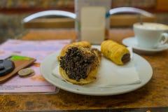 Schokolade cannoli auf weißer Platte mit Kaffee, Euromünzen Lizenzfreie Stockfotos