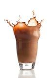 Schokolade, die in Glas spritzt stockbilder